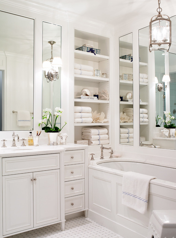 Small elegant master white tile mosaic tile floor bathroom photo in New York with an undermount sink, white cabinets, marble countertops, an undermount tub, white walls, raised-panel cabinets and white countertops