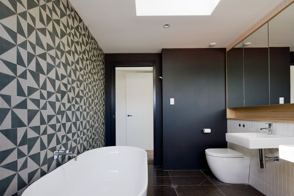 Inspiration for a contemporary black and white tile freestanding bathtub remodel in Sydney with a wall-mount sink and a one-piece toilet