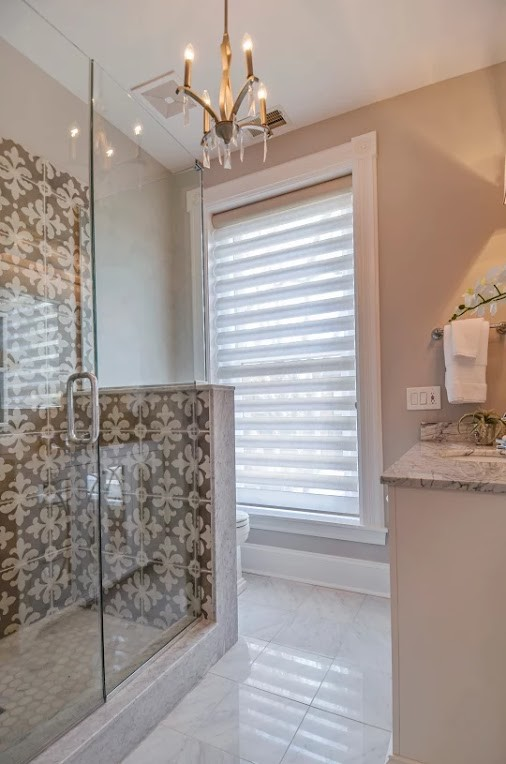 Mid-sized transitional 3/4 white tile porcelain tile and gray floor alcove shower photo in Chicago with raised-panel cabinets, white cabinets, gray walls, an undermount sink, marble countertops and a hinged shower door