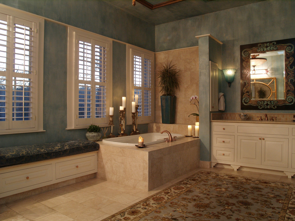 Tuscan drop-in bathtub photo in Austin with raised-panel cabinets and beige cabinets