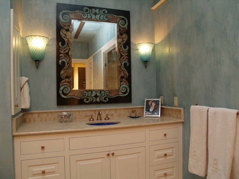 Inspiration for a mediterranean beige tile and mosaic tile bathroom remodel in Austin with an undermount sink, raised-panel cabinets and beige cabinets