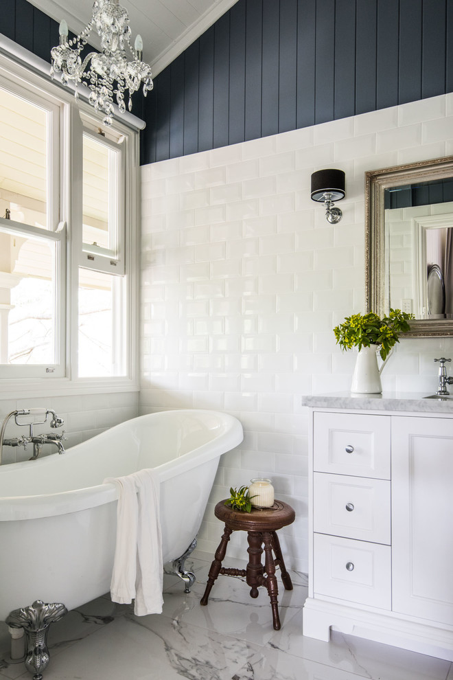 Inspiration for a mid-sized country master white tile and subway tile porcelain tile claw-foot bathtub remodel in Brisbane with white cabinets, blue walls, a drop-in sink, marble countertops and recessed-panel cabinets