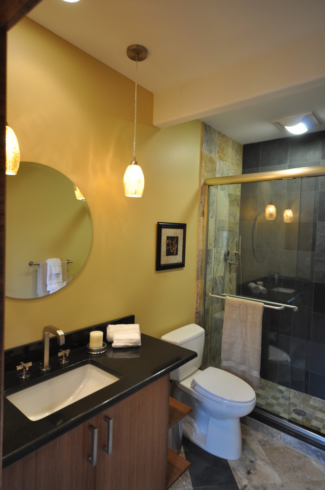 Example of a large trendy 3/4 gray tile and stone tile slate floor alcove shower design in Philadelphia with an undermount sink, flat-panel cabinets, brown cabinets, granite countertops, a two-piece toilet and yellow walls