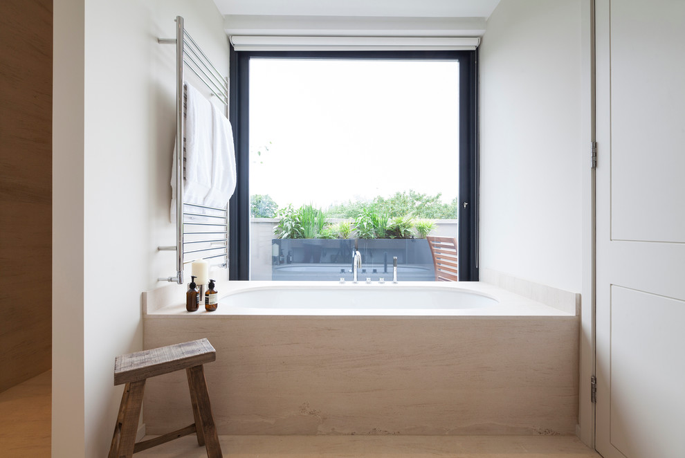Inspiration for a scandinavian master bathroom remodel in London with an undermount tub and white walls