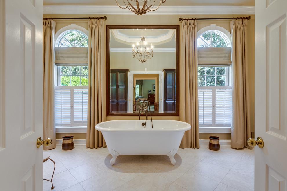 Claw-foot bathtub - traditional beige floor claw-foot bathtub idea in DC Metro with brown walls