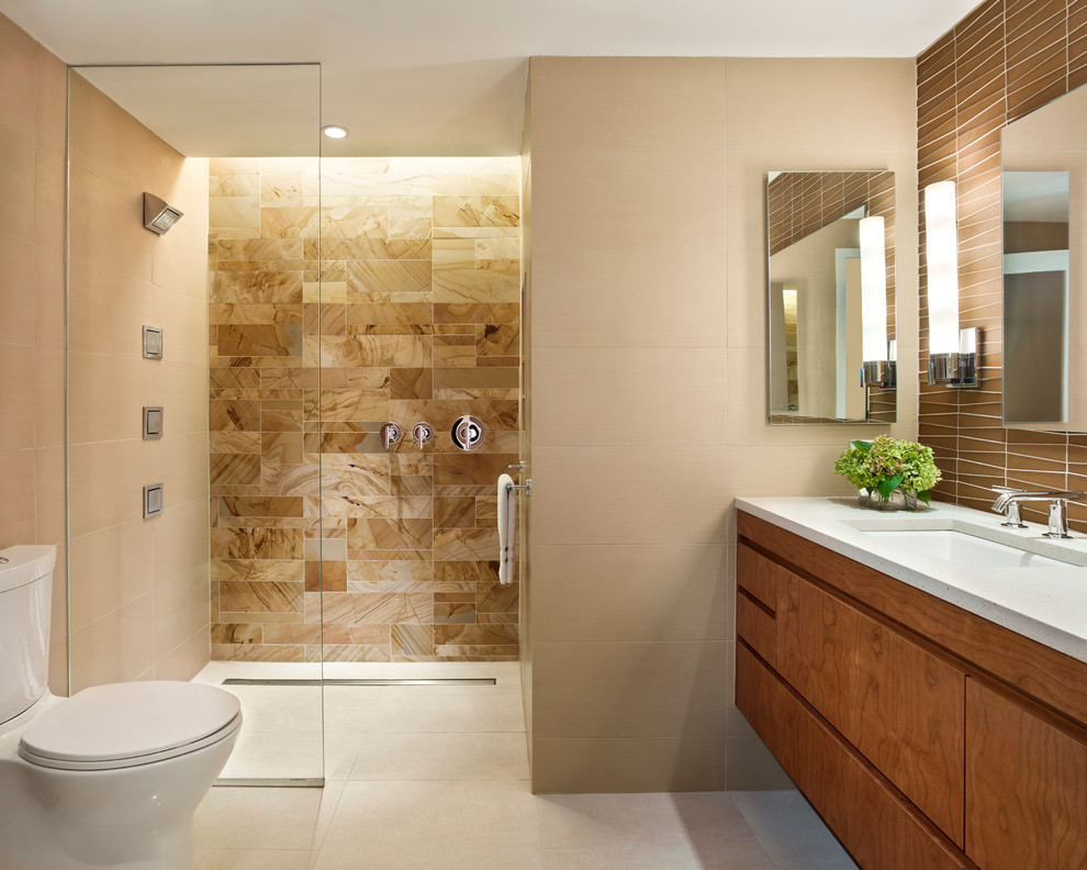Example of a trendy beige tile and stone tile porcelain tile and beige floor walk-in shower design in Philadelphia with an undermount sink, flat-panel cabinets, medium tone wood cabinets, beige walls and white countertops