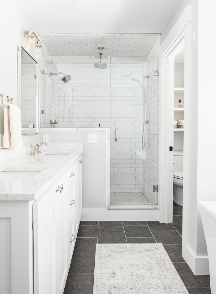 Example of a mid-sized transitional master white tile and subway tile slate floor and gray floor bathroom design in Portland Maine with shaker cabinets, white cabinets, gray walls, an undermount sink, marble countertops and a hinged shower door