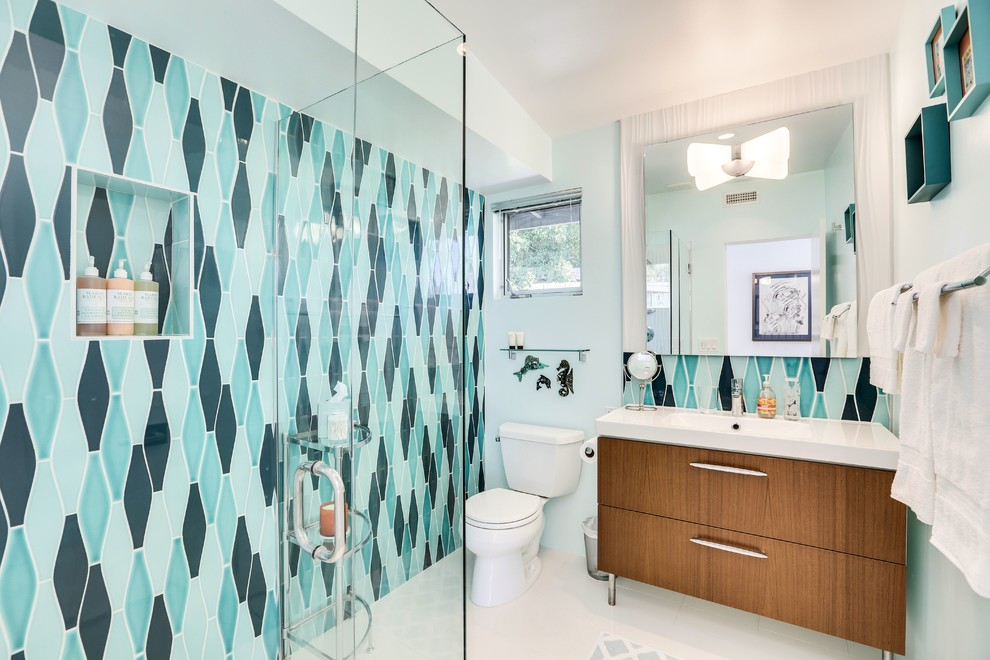 Inspiration for a large 1960s 3/4 white tile and stone slab ceramic tile bathroom remodel in Los Angeles with flat-panel cabinets, light wood cabinets, a one-piece toilet, blue walls, a trough sink and solid surface countertops