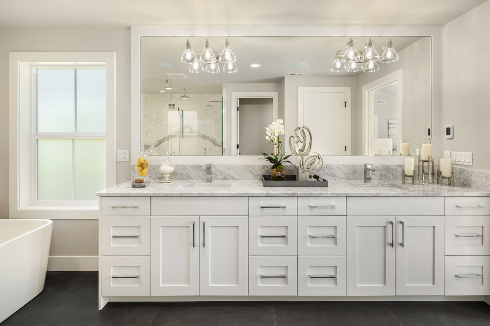 Country gray floor and double-sink bathroom photo in Seattle with shaker cabinets, white cabinets, gray walls, an undermount sink and gray countertops
