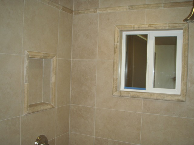 Porcelain wall tile with travertine detail at crown, window wrap and niche tropical-bathroom