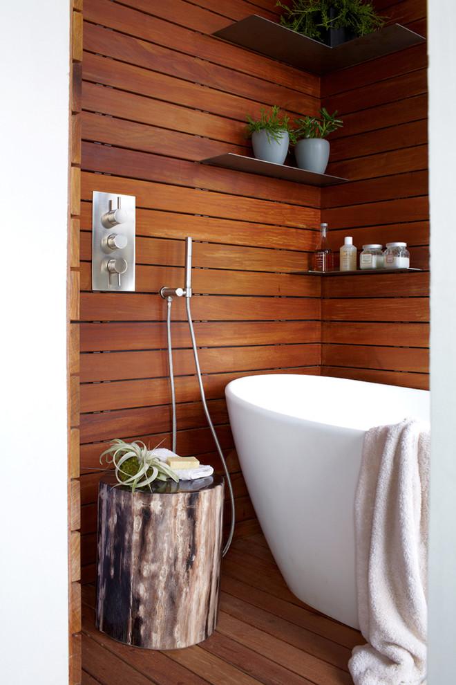 Large minimalist master medium tone wood floor freestanding bathtub photo in New York