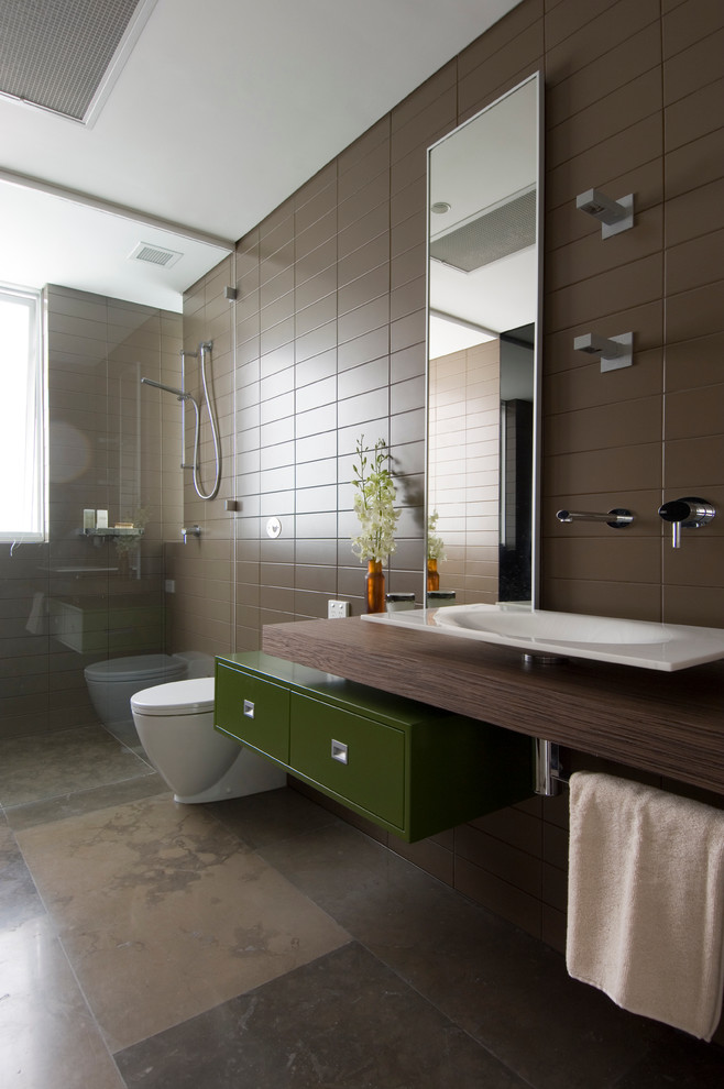 Example of a minimalist brown tile walk-in shower design in Sydney with a vessel sink, flat-panel cabinets, green cabinets, wood countertops, brown walls and brown countertops