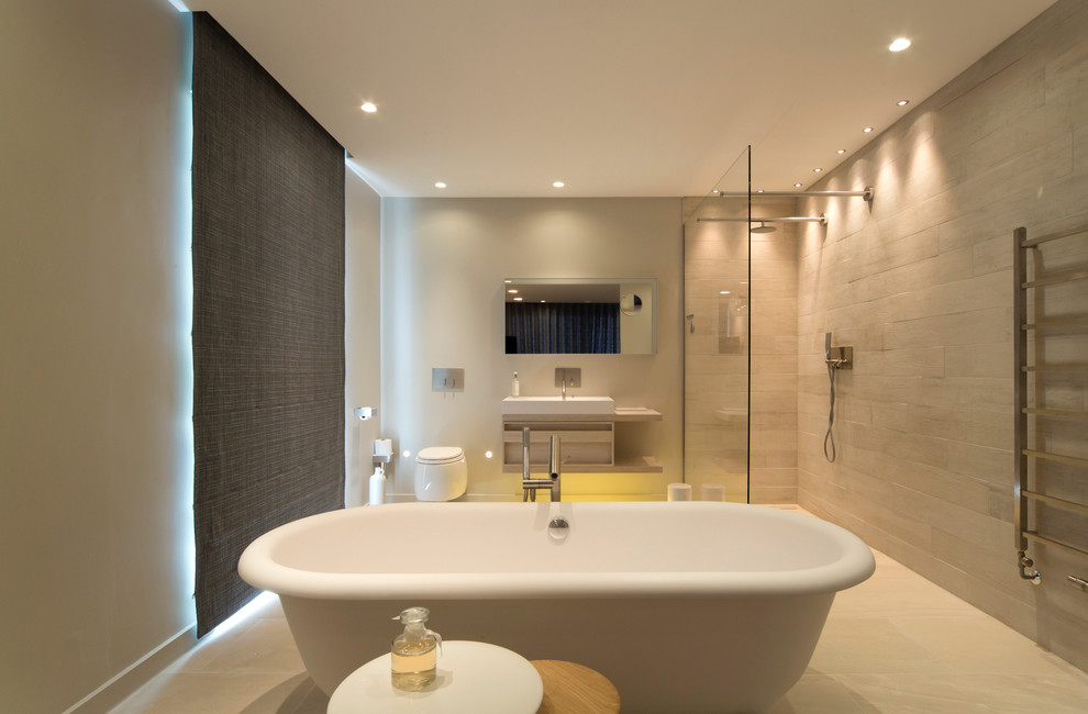 Bathroom - contemporary beige tile bathroom idea in London with a wall-mount toilet, white walls and a trough sink