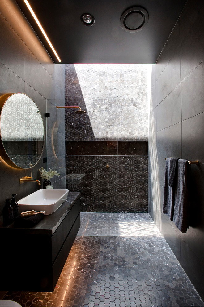 Trendy 3/4 black tile and gray tile mosaic tile floor and black floor bathroom photo in Sydney with flat-panel cabinets, black cabinets, black walls and a vessel sink
