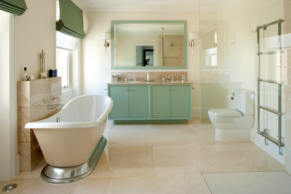 Elegant beige floor freestanding bathtub photo in London with flat-panel cabinets and green cabinets