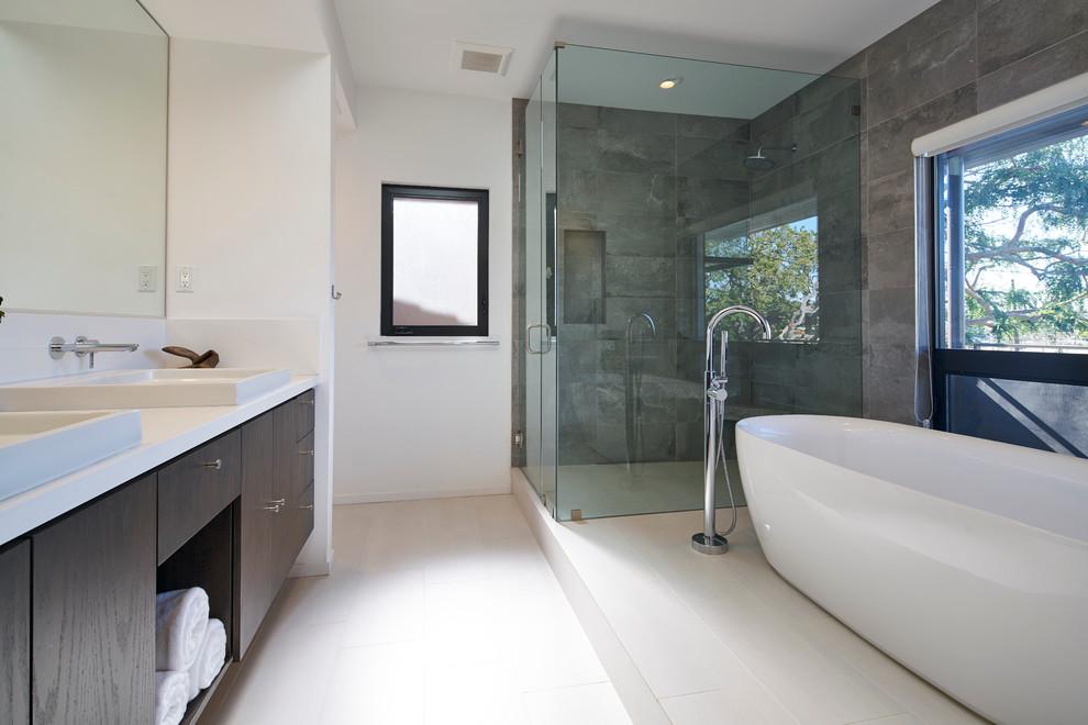 ロサンゼルスの広いコンテンポラリースタイルのおしゃれなマスターバスルーム (フラットパネル扉のキャビネット、濃色木目調キャビネット、置き型浴槽、白いタイル、磁器タイル、ベッセル式洗面器、クオーツストーンの洗面台、バリアフリー、白い壁、磁器タイルの床、白い洗面カウンター) の写真