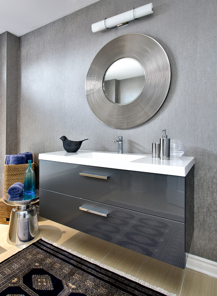 Bathroom - mid-sized contemporary beige tile and porcelain tile ceramic tile bathroom idea in Montreal with flat-panel cabinets, gray cabinets, gray walls, an integrated sink and a one-piece toilet
