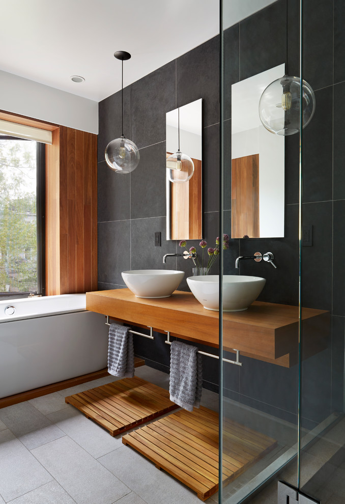 Example of a trendy black tile and slate tile drop-in bathtub design in New York with a vessel sink, wood countertops and brown countertops