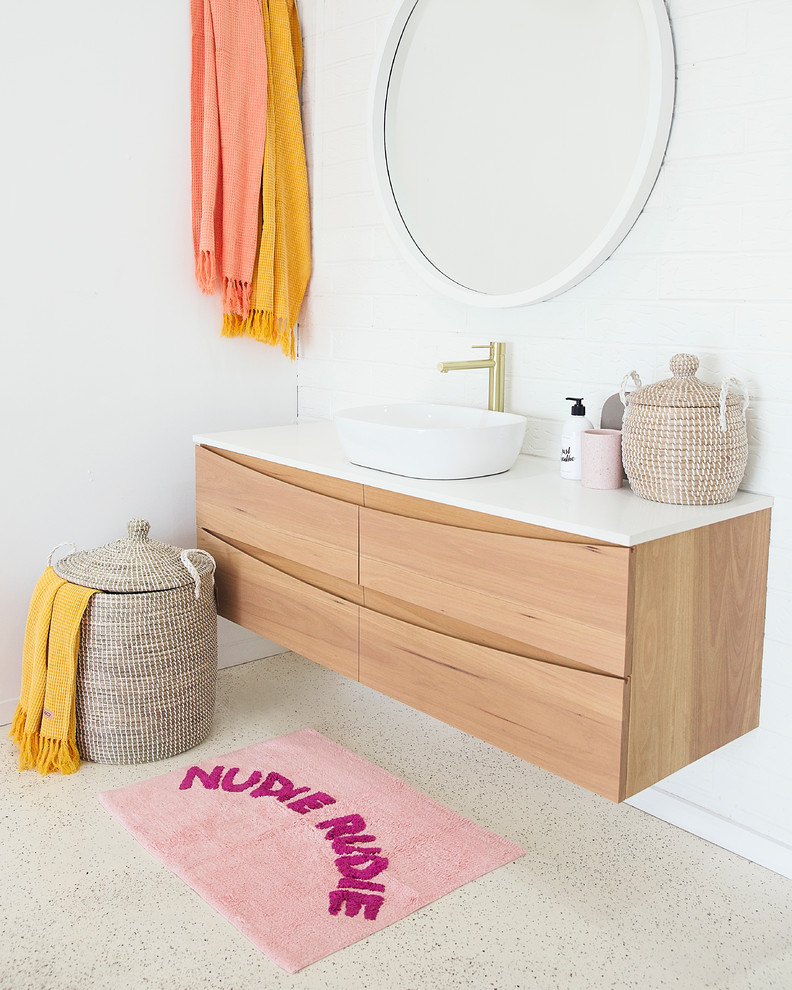 Bathroom - coastal 3/4 concrete floor and beige floor bathroom idea in Sunshine Coast with flat-panel cabinets, light wood cabinets, white walls, a vessel sink and white countertops