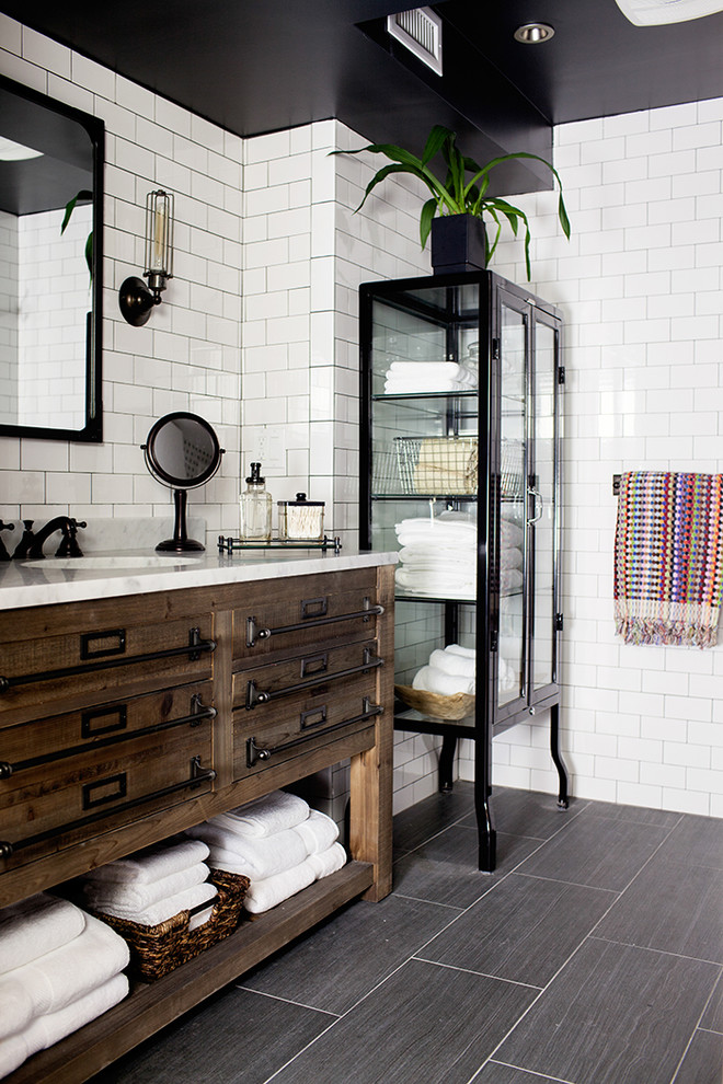 Transitional white tile and subway tile ceramic floor bathroom photo in New York with an undermount sink, marble countertops, black walls and flat-panel cabinets