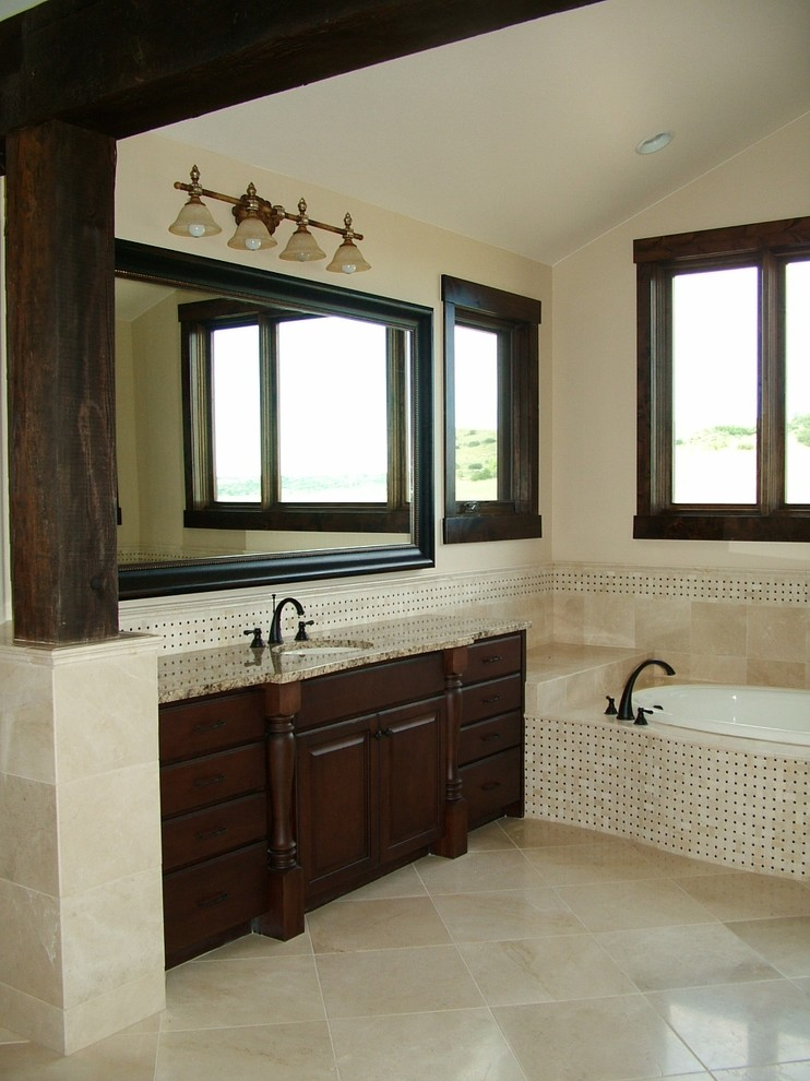 Elegant beige tile drop-in bathtub photo in Denver with an undermount sink, dark wood cabinets and raised-panel cabinets