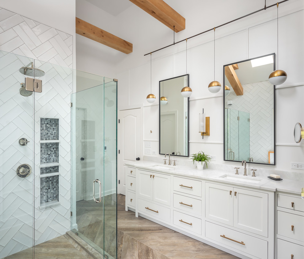 Bathroom - mid-sized farmhouse master white tile and ceramic tile porcelain tile and brown floor bathroom idea in Raleigh with recessed-panel cabinets, white cabinets, a two-piece toilet, white walls, an undermount sink, marble countertops, a hinged shower door and white countertops