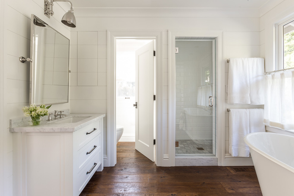 Mid-sized elegant white tile and porcelain tile marble floor bathroom photo in San Francisco with medium tone wood cabinets, a one-piece toilet, white walls, an undermount sink and marble countertops