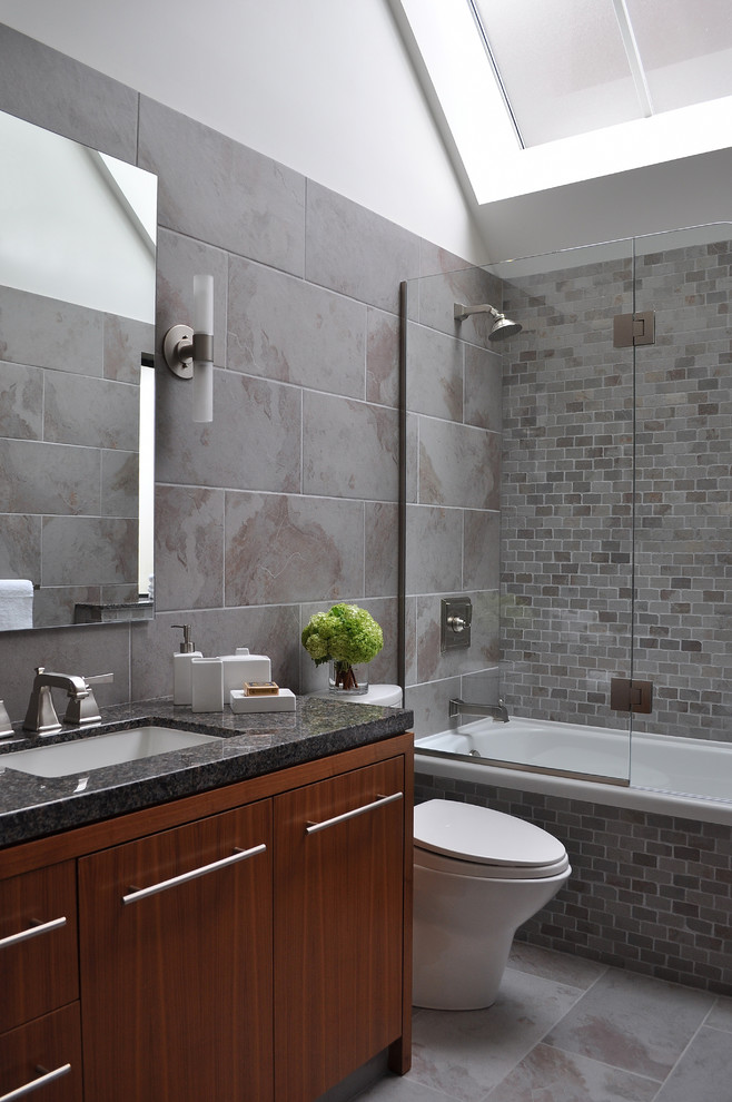 Trendy gray tile bathroom photo in Vancouver with an undermount sink, flat-panel cabinets and dark wood cabinets
