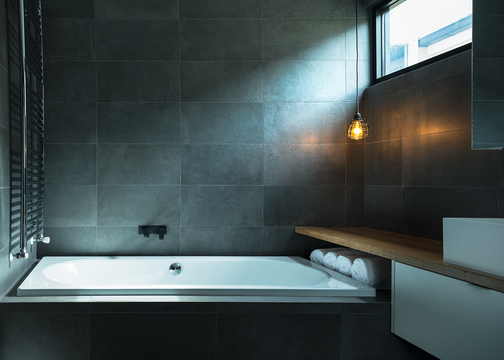 Drop-in bathtub - mid-sized industrial master black tile and porcelain tile drop-in bathtub idea in Melbourne with a vessel sink, flat-panel cabinets, white cabinets, wood countertops, black walls and brown countertops
