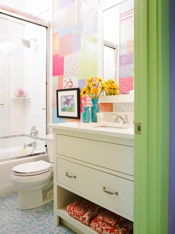 Example of a mid-sized eclectic kids' gray tile, multicolored tile, white tile and porcelain tile mosaic tile floor bathroom design in Atlanta with white cabinets, flat-panel cabinets, a two-piece toilet, multicolored walls, an undermount sink, solid surface countertops and white countertops