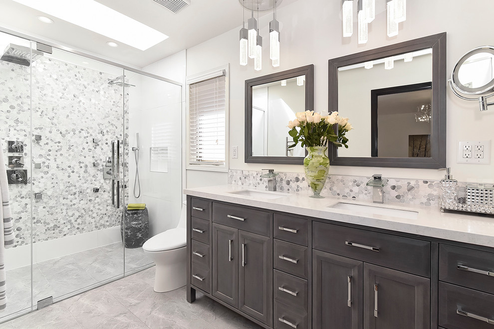 Double shower - contemporary master gray tile and pebble tile porcelain tile double shower idea in Calgary with recessed-panel cabinets, white walls, marble countertops and an undermount sink