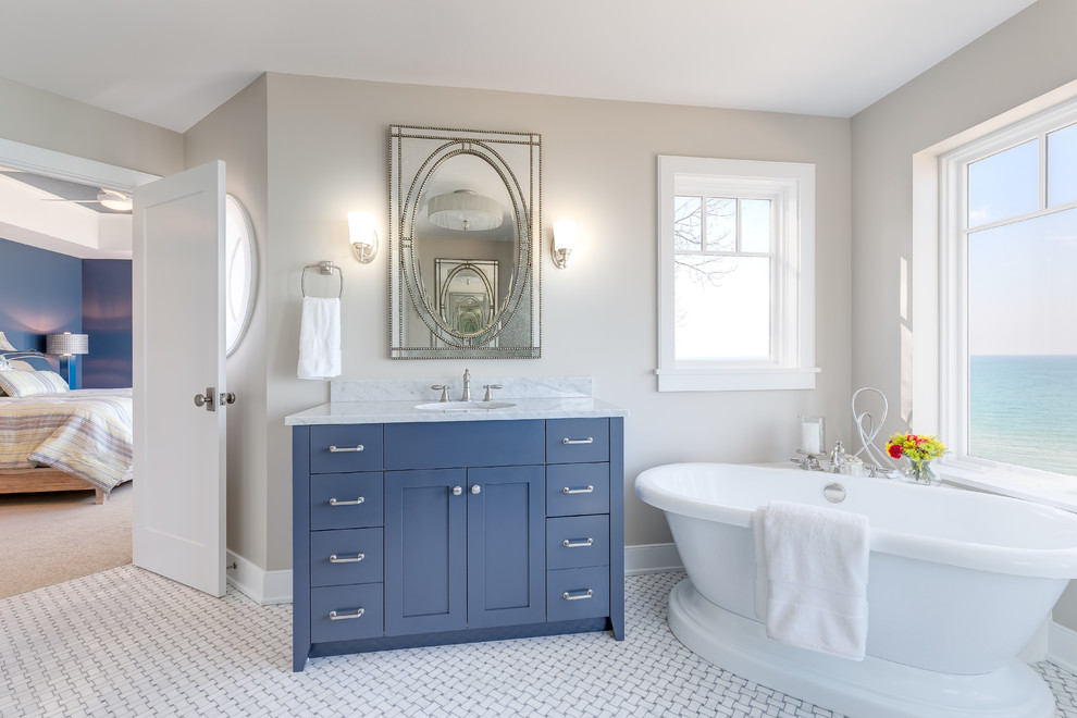 Freestanding bathtub - coastal master freestanding bathtub idea in Chicago with blue cabinets, beige walls and an undermount sink