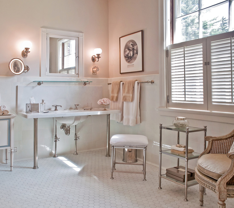 Example of a classic bathroom design in Boston with a console sink, marble countertops and pink walls