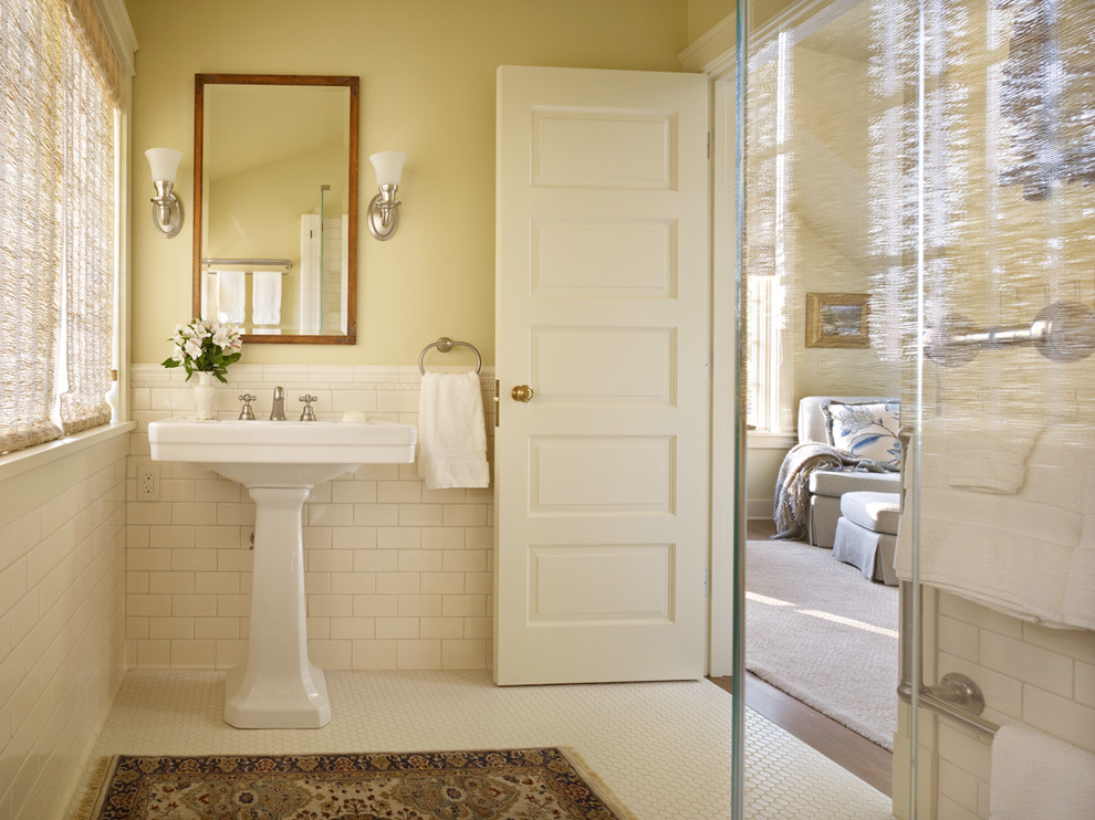 Corner shower - traditional mosaic tile floor corner shower idea in Seattle with a pedestal sink and yellow walls