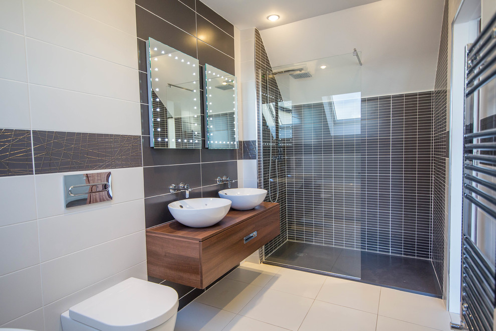 Example of a mid-sized trendy multicolored tile ceramic tile and white floor bathroom design in Cork with a one-piece toilet, flat-panel cabinets, medium tone wood cabinets, multicolored walls, wood countertops and brown countertops