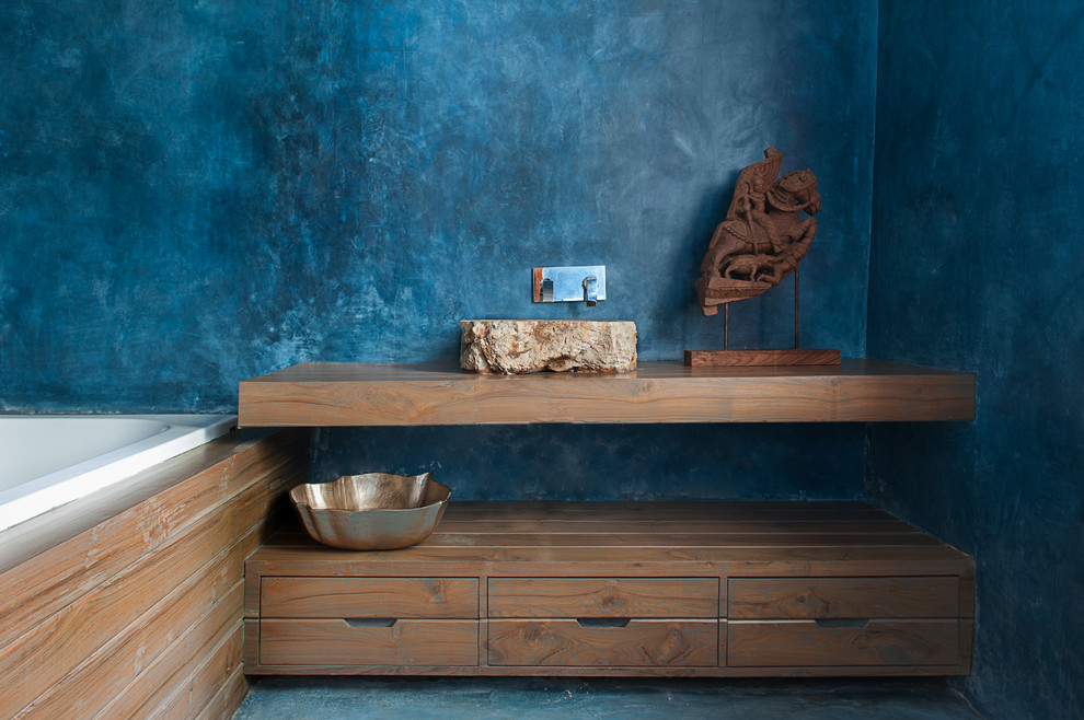 Example of a zen drop-in bathtub design in Delhi with open cabinets, medium tone wood cabinets, blue walls, wood countertops and brown countertops