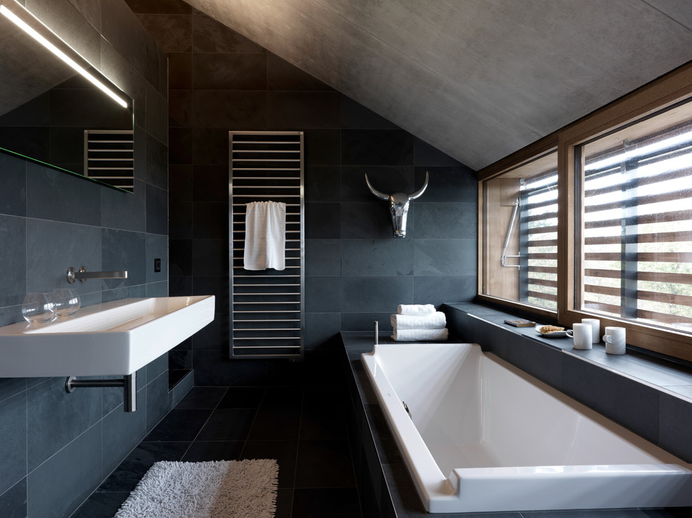 Example of a trendy slate tile bathroom design in Orange County with a wall-mount sink