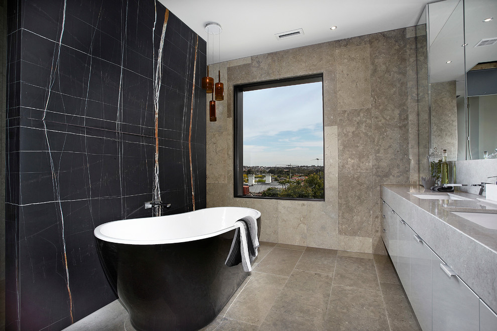Trendy limestone tile freestanding bathtub photo in Melbourne with black walls and gray countertops