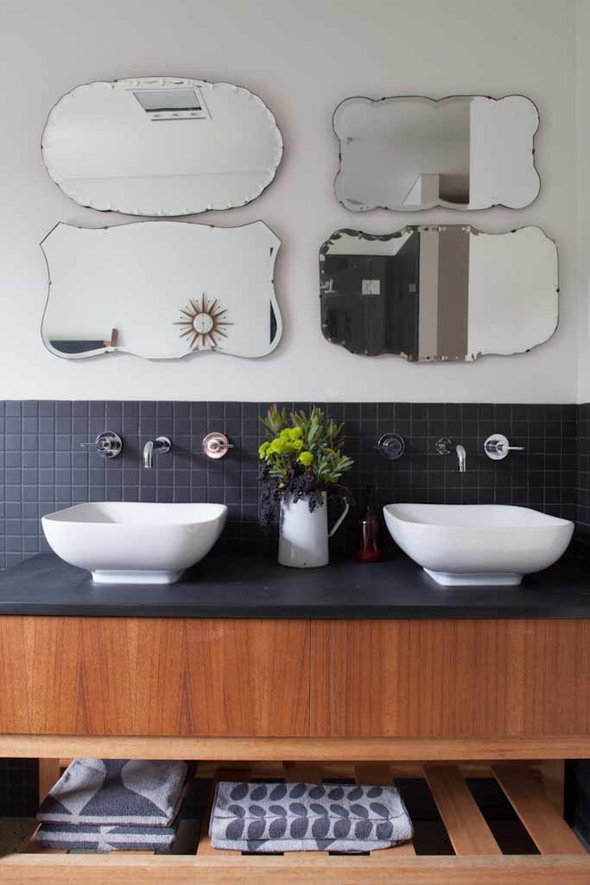Bathroom - contemporary black tile bathroom idea in Adelaide with a vessel sink, open cabinets, medium tone wood cabinets and black countertops