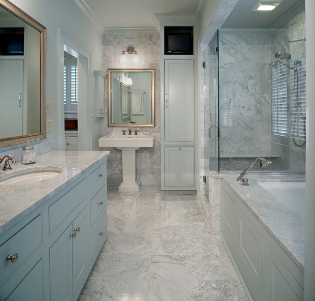 Example of a classic white tile corner shower design in New Orleans with a pedestal sink, blue cabinets, an undermount tub and recessed-panel cabinets