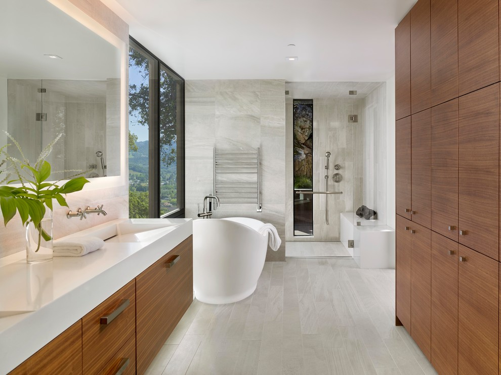 Example of a trendy master gray tile gray floor bathroom design in San Francisco with flat-panel cabinets, medium tone wood cabinets, gray walls, an integrated sink and white countertops