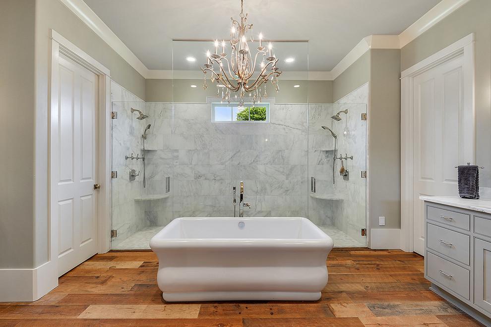 Modelo de cuarto de baño principal, tradicional renovado, grande, con puertas de armario grises, bañera exenta, ducha doble, suelo de madera en tonos medios, armarios estilo shaker y ducha con puerta con bisagras