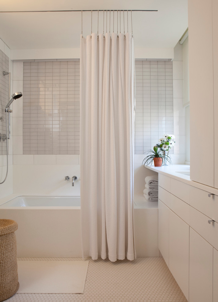 Inspiration for a contemporary gray tile tub/shower combo remodel in New York with an undermount sink, flat-panel cabinets, white cabinets and an undermount tub
