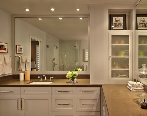 This contemporary bathroom features a large mirror, frosted glass-faced cabinets, and two sinks, one on either side of the L-shaped vanity.