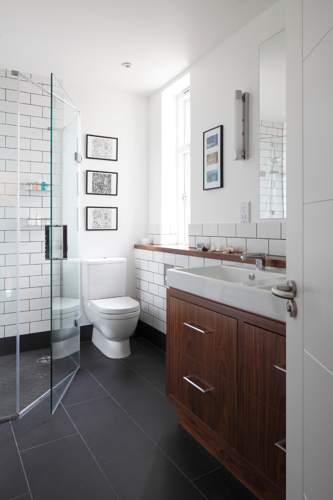 Inspiration for a small contemporary kids' white tile and ceramic tile gray floor, slate floor and double-sink corner shower remodel in London with an integrated sink, flat-panel cabinets, dark wood cabinets, white walls, a one-piece toilet, wood countertops, a hinged shower door, brown countertops and a built-in vanity