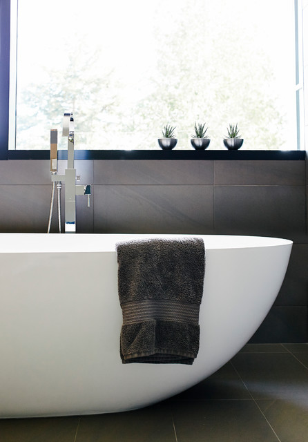 Bathroom - mid-sized contemporary master gray tile and porcelain tile porcelain floor bathroom idea in Vancouver with a vessel sink, flat-panel cabinets, light wood cabinets, engineered quartz countertops, a wall-mount toilet and gray walls