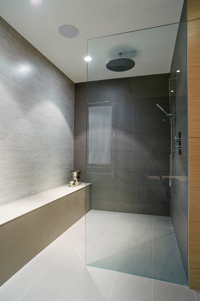 Inspiration for a mid-sized contemporary master gray tile and porcelain tile porcelain floor bathroom remodel in Vancouver with a vessel sink, flat-panel cabinets, light wood cabinets, quartz countertops and gray walls