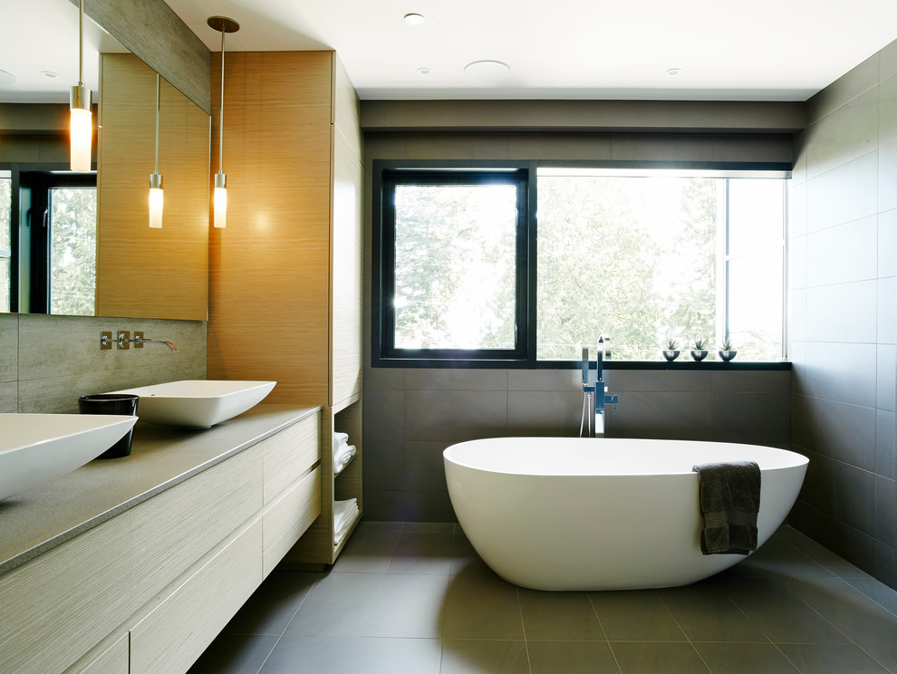 Bathroom - mid-sized contemporary master gray tile and porcelain tile porcelain floor bathroom idea in Vancouver with a vessel sink, flat-panel cabinets, light wood cabinets, quartz countertops, a wall-mount toilet and gray walls