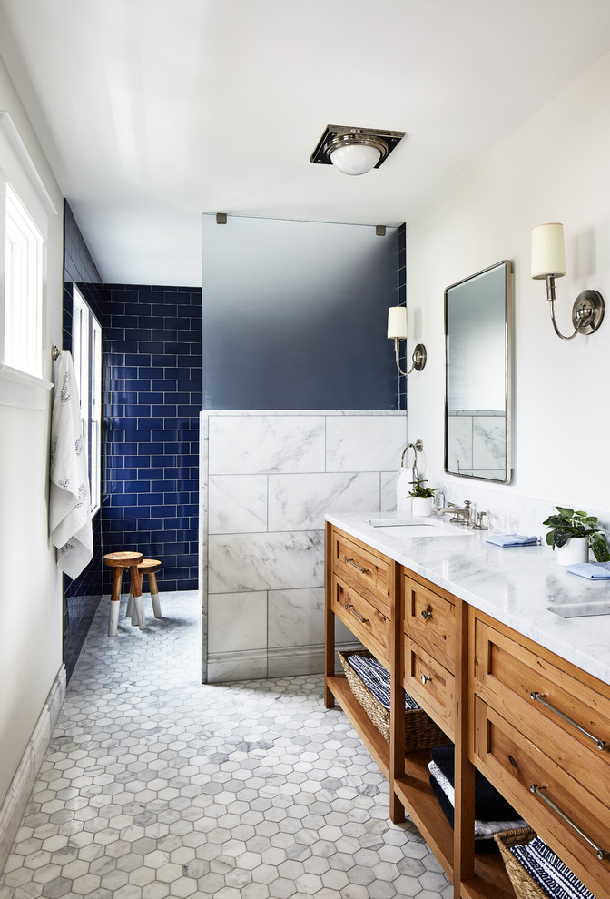 Example of a beach style blue tile and subway tile white floor bathroom design in DC Metro with furniture-like cabinets, medium tone wood cabinets, white walls, an undermount sink and white countertops