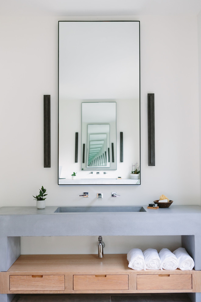 Example of a beach style bathroom design in Nashville with flat-panel cabinets, light wood cabinets, white walls, an integrated sink, gray countertops and concrete countertops